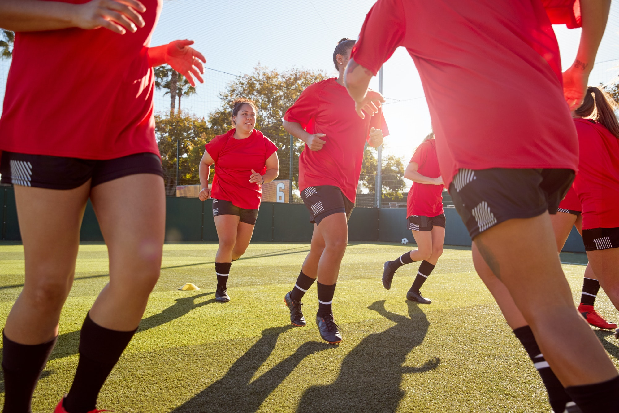 womens-football-team-run-whilst-training-for-soccer-match-on-outdoor-astro-turf-pitch.jpg